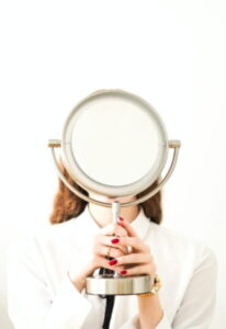 woman in white long sleeve shirt holding magnifying glass