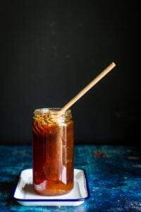 brown beverage in clear mason jar with sstirrer